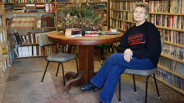 Elsie Eiler poses in the 5,000 book library in the village of Monowi, Nebraska April 28, 2011. Eiler is the person living in Monowi making it the only incorporated town, village or city in the United States with only one resident.  The library was the dream of her late husband Rudy a devoted reader. REUTERS/Rick Wilking (UNITED STATES) - LM2E7540PMJ01