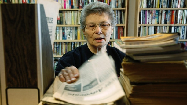 Elsie Eiler talks to a visitor in the 5,000 book library as she looks through old newspapers in the village of Monowi, Nebraska April 28, 2011. Eiler is the person living in Monowi making it the only incorporated town, village or city in the United States with only one resident.  The library was the dream of her late husband Rudy a devoted reader. REUTERS/Rick Wilking (UNITED STATES) - LM2E7540PX101