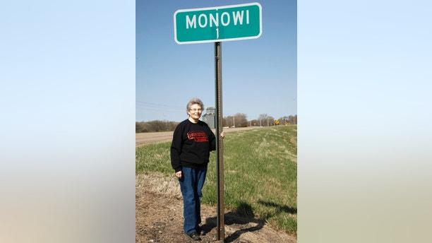 Elsie Eiler poses with the town population sign outside of the village of Monowi, Nebraska April 28, 2011 with the abandoned town grain elevator in the background.  Eiler is the person living in Monowi making it the only incorporated town, village or city in the United States with only one resident.  REUTERS/Rick Wilking (UNITED STATES) - LM2E7540PXC01