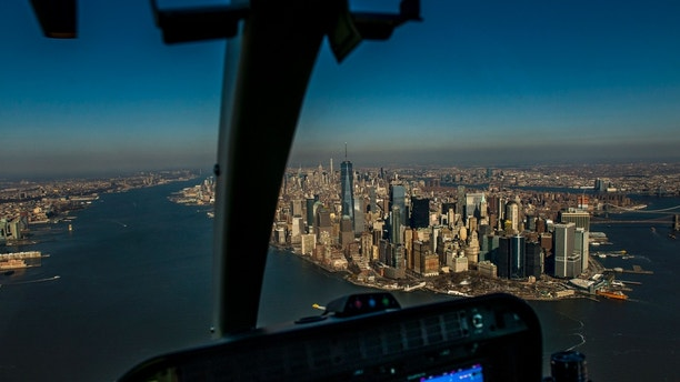 Financial District in Lower Manhattan, New York City via helicopter. Horizontal composition. Helicopter moving forward via Hudson River and Lower Manhattan appearing well in NY, USA.