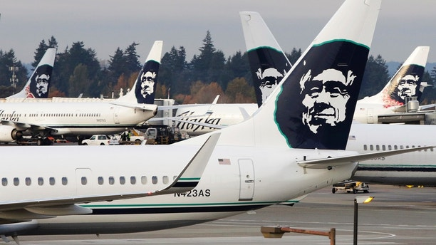 A ground crew member walks near Alaska Airlines planes parked at Seattle-Tacoma International Airport in SeaTac, Washington October 30, 2013. Voters in the working-class Seattle suburb of SeaTac, which encompasses the region's main airport, will decide on November 5, 2013 whether to enact one of the country's highest minimum wages in a ballot measure supporters hope will serve as a model for similar efforts elsewhere. Paul McElroy, a spokesman for SeaTac-based Alaska Airlines, which lost a court battle to keep a minimum wage initiative off the ballot, said its passage might prompt the airline to reroute some flights as a cost-saving measure. Amid debate about income inequality in America, the ballot initiative in SeaTac, Washington, would mandate that 6,300 workers at Sea-Tac International Airport and nearby hotels, car rental agencies and parking lots receive a minimum hourly wage of $15, more than double the current federal minimum wage of $7.25. Picture taken October 30, 2013. REUTERS/Jason Redmond (UNITED STATES - Tags: POLITICS BUSINESS TRANSPORT EMPLOYMENT TPX IMAGES OF THE DAY) - GM1E9B51OMJ01