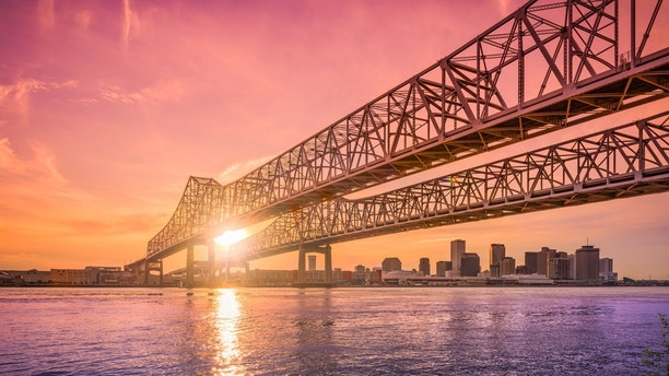 New Orleans, Louisiana, USA at Crescent City Connection Bridge over the Mississippi River during sunset.