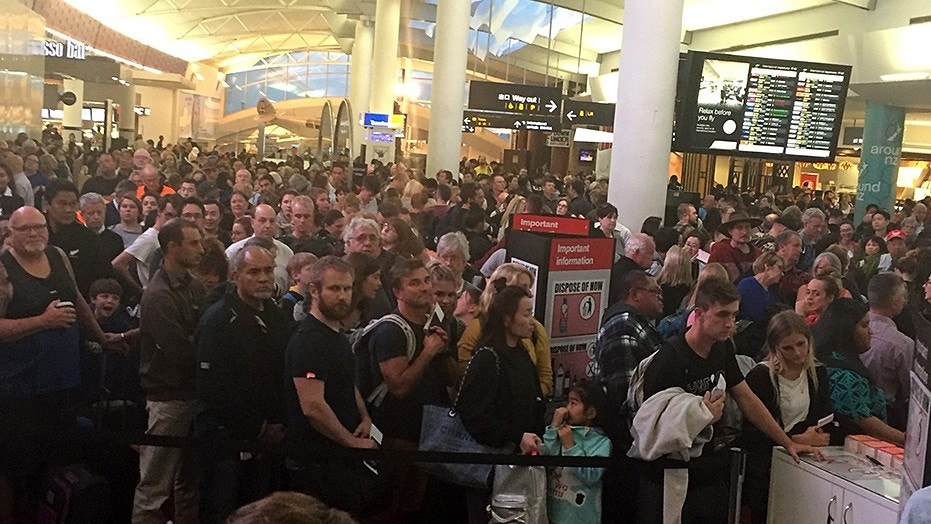 Crowds of passengers await the re-opening of airport security after a woman took a knife into the Auckland Airport's international terminal.