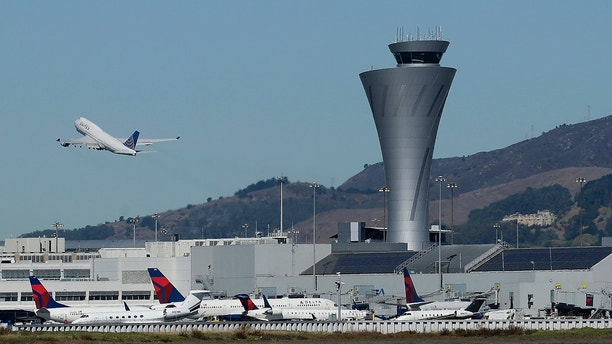 FILE - In this Oct. 24, 2017, file photo, the air traffic control tower is in sight as a plane takes off from San Francisco International Airport in San Francisco. Federal authorities have determined most of the close-calls reported since December 2016 at the busy San Francisco International Airport were caused by pilots. The East Bay Times reports Wednesday, May 2, 2018, the Federal Aviation Administration found that in three instances planes lined up for wrong runways and taxiways due to pilot error. A fourth plane was mistakenly cleared to land in the wrong runway by a tower controller.(AP Photo/Jeff Chiu, File)'