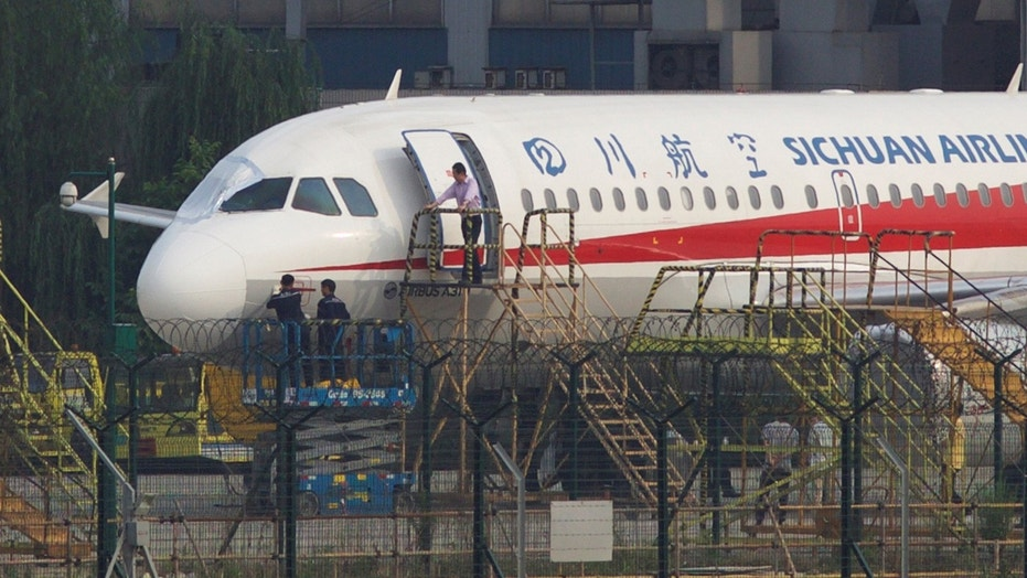 May 14: Workers inspect a Sichuan Airlines aircraft that made an emergency landing after a windshield on the cockpit broke off, at an airport in Chengdu, Sichuan province