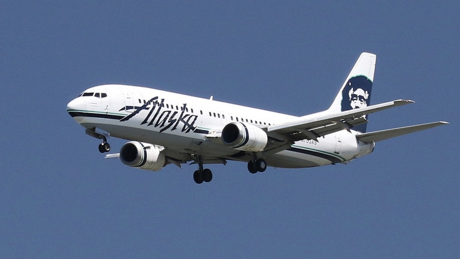 An Alaska Airlines flight landed safely in Anchorage after a passenger stripped down and had to be detained.