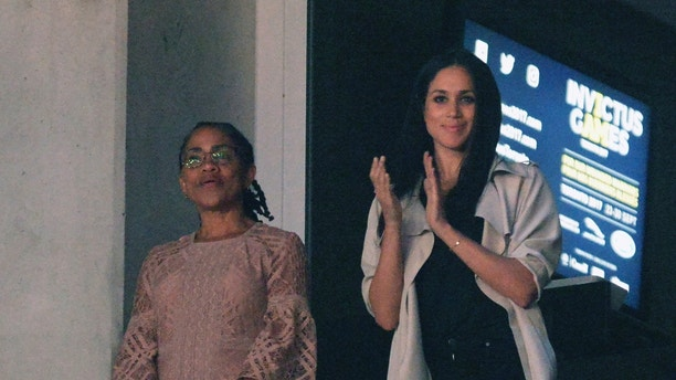 FILE - In this Saturday, Sept. 30, 2017 file photo, Meghan Markle, right, watches the closing ceremonies of the Invictus Games with her mother Doria Ragland in Toronto. Royal officials say Meghan Markle's divorced parents will come to London before her May 19 wedding to Prince Harry and will meet with Queen Elizabeth II and other royals. Harry's press secretary Jason Knauf said Friday, May 4, 2018 that Thomas Markle and Doria Ragland will arrive during the week before the Saturday wedding so they will have time to meet Harry's family. (Nathan Denette/The Canadian Press via AP, File)