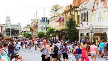 Orlando, USA - August 4, 2013: View of the people and families that cross Main Street USA, the entrance to Magic Kingdom amusement park at Walt Disney World with restaurants and souvenir stores. Shoot at mid day during the high summer season.