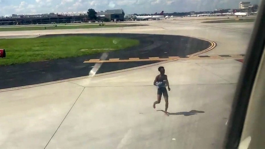 A passenger was arrested after jumping off a plane onto the tarmac in his underwear.
