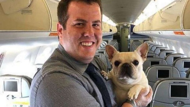Flight attendant Renaud Fenster poses with Darcy on the Massachusetts-bound flight