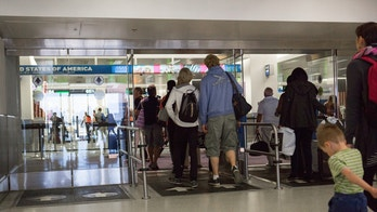 Miami, United States - June 20, 2015: Passengers have landed in Miami International Airport on international flights from other countries. They are walking through glass doors to enter the United States Customs area. They will have to show their passports in order to leave the airport and enter the country. Miami International Airport is the major airport in Florida for long haul international flights and the largest gateway between the US and Latin America, making the customs area very busy.