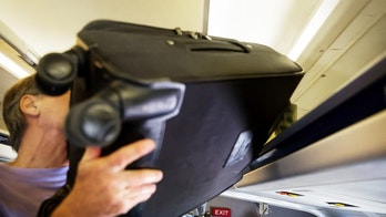 A senior man putting a heavy piece of luggage in the luggage compartment of an airplane.  rr