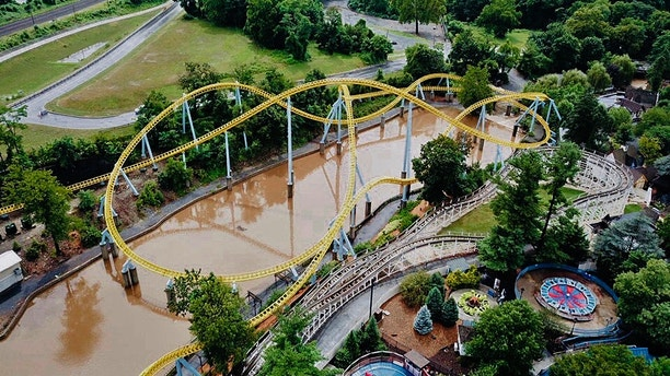 In this Monday, July 23, 2018, aerial image provided by The Wyse Choice photography in Hershey, Pa., muddy brown floodwaters in Spring Creek flow beneath the Skyrush roller coaster, in yellow, and past the Comet roller coaster, in white, at the Hersheypark theme park in Hershey, Pa. Hersheypark and the neighboring ZooAmerica wildlife park closed due to flooding Monday, July 23, 2018, after three days of rain in the central and eastern parts of Pennsylvania that caused Spring Creek to flood and the nearby Swatara Creek to approach moderate flood stage. Giant Center arena is visible in the top right corner. (The Wyse Choice via AP)