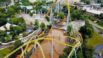 In this Monday, July 23, 2018, aerial image provided by The Wyse Choice photography in Hershey, Pa., muddy brown floodwaters in Spring Creek flow beneath the Skyrush roller coaster, in yellow, and the Comet roller coaster, in white, at the Hersheypark theme park in Hershey, Pa. Hersheypark and the neighboring ZooAmerica wildlife park closed due to flooding Monday, July 23, 2018, after three days of rain in the central and eastern parts of Pennsylvania that caused Spring Creek to flood and the nearby Swatara Creek to approach moderate flood stage. The roof of Hersheypark's Carrousel ride is visible at left, and the scenic Kissing Tower ride and the cocoa bean silos and twin smokestacks of The Hershey Company's original chocolate factory, largely demolished in 2013 and 2014, are visible top left of center. (The Wyse Choice via AP)