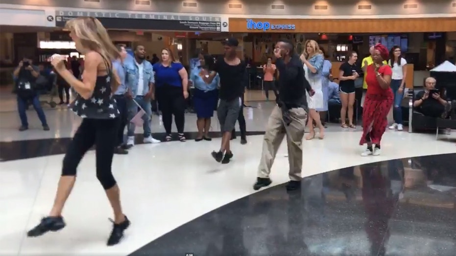 An Alabama woman surprised her husband with a flash mo at the airport, but his flight was delayed and he didn't make it in time.