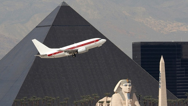 A Boeing 737 (737-600) jetliner, registered to the U.S. Department of the Air Force, passes the Luxor Hotel/Casino as it takes off at McCarran International Airport in Las Vegas, Nevada on Mar. 3, 2016. The jet is rumored to fly contactors to and from Area 51 and is nicknamed Janet Airlines.  (Larry MacDougal via AP)