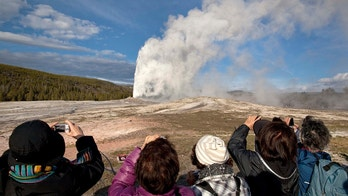 FILE - In this May 21, 2011, file photo, tourists photograph Old Faithful erupting on schedule late in the afternoon in Yellowstone National Park, Wyo. Yellowstone National Park officials say they've ticketed a man caught on video walking dangerously close to Old Faithful geyser. (AP Photo/Julie Jacobson, File)
