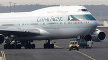 An airport apron controller vehicle is pictured in front of a Cathay Pacific Boeing B747-400 Aircraft on the runway at Frankfurt's airport February 21, 2012. Strikes at Frankfurt airport, Germany's largest, will continue until the weekend, the GdF union, resulting in more flight cancellations and delays. Just under 200 apron control workers, such as those who guide aircraft to parking places, are striking over a pay dispute with Fraport, which runs the airport. REUTERS/Alex Domanski (GERMANY - Tags: BUSINESS TRANSPORT EMPLOYMENT) - RTR2Y700