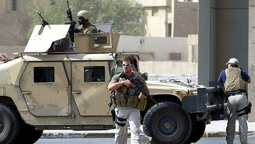 July 2005: Blackwater guards secure the site of a roadside bomb attack near the Iranian embassy in central Baghdad. (AFP)