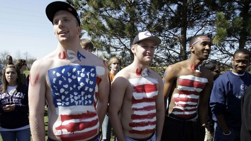 March 23: Goshen College students, left to right, Taylor TenHarmsel, Sean Doering, and Nate West Jr., painted their bodies to represent an American flag for the Goshen College baseball game in Goshen, Ind.