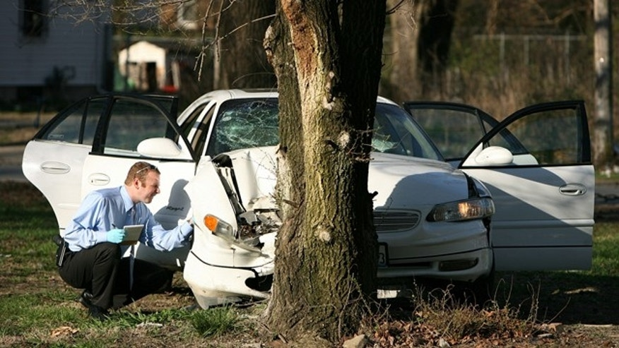 April 1: A crime scene investigator combs the wreckage of Washington Park Mayor John Thornton's car.