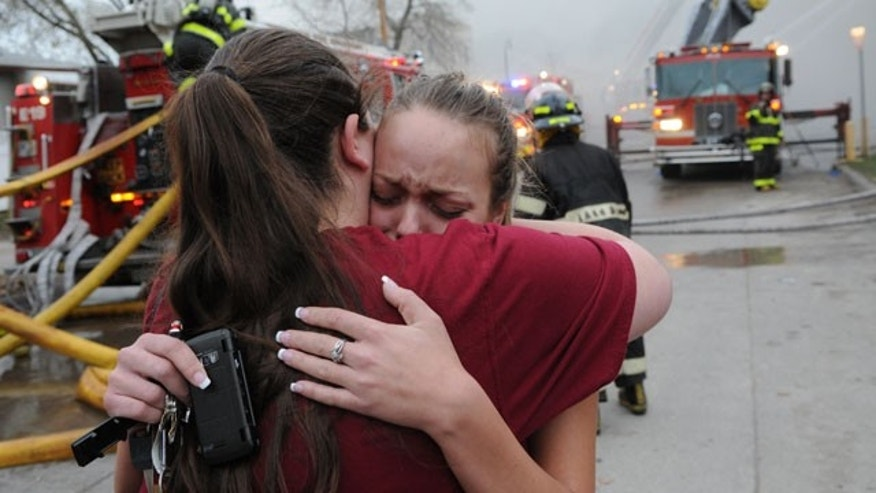April 2: An unidentified friend comforts Rosie Bell, right, an employee of McMahon's Pub, as firefighters put out a fire on the second floor of a building that houses McMahon's Pub in south Minneapolis, Minn.