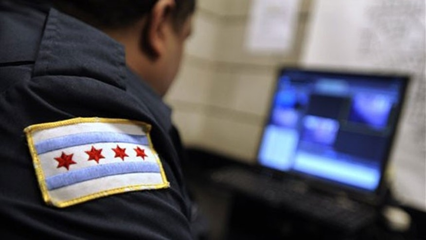 Chicago Police Officer Tony Washington watches surveillance videos at the 18th District Chicago Police Station.