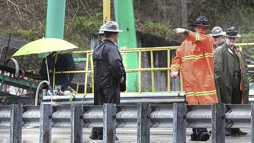 April 8: Law officers move the media down the road away from the mine entrance to Performance Coal Company, in Montcoal, W.Va. (AP)