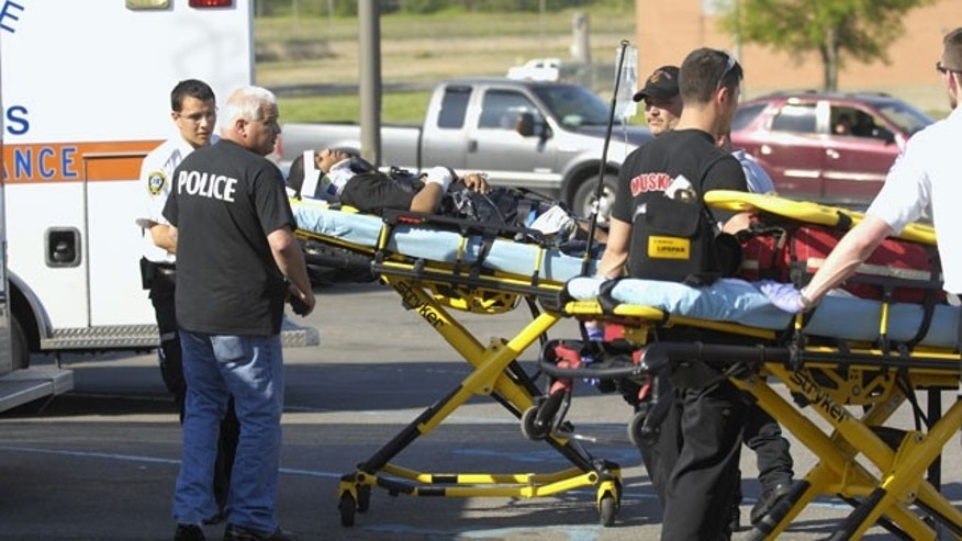 April 10: Muskogee Police Capt. Scott Shields escorts medics as they load an injured man into an ambulance in Muskogee, Okla.