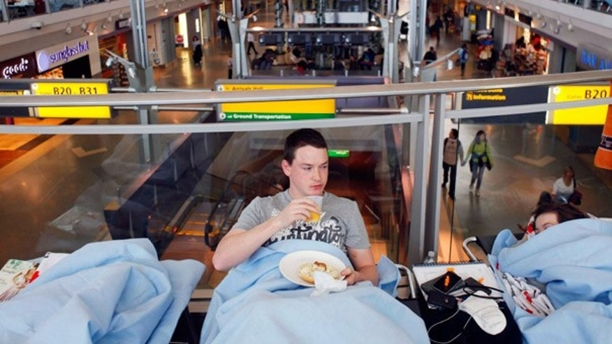 April 19: Huw Thomas, of England, eats his breakfast in his cot at JFK Airport in New York. He's been stranded at the airport with his family since Friday.