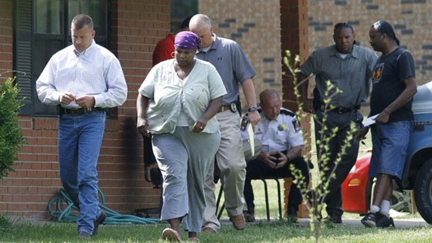 Investigators speak to neighbors of Richard Barrett, a white supremacist lawyer with a knack for publicity, who was found stabbed to death in his burning house in Rankin County near Pearl, Miss., Thursday, April 22, 2010. Barrett, a New York City native and Vietnam War veteran, moved to Mississippi in 1966, and soon after, he began traveling the country to promote anti-black and anti-immigrant views, and founded a supremacist group called the Nationalist Movement.