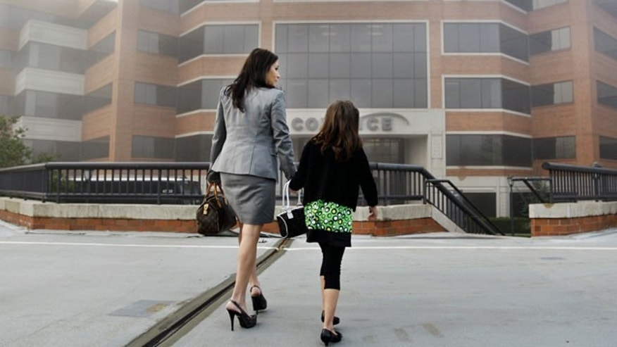 "Alicia Agigliaro arrives at work in an early morning fog, Thursday, April 22, 2010, in Princeton, N.J., as she brings along her 7-year-old daughter Eliana Agigliaro. School districts across across the country are asking parents to keep their kids in the classroom instead of bringing them to the office during Thursday's ""Take Our Daughters and Sons to Work Day,"" saying the annual event disrupts learning at an increasingly crucial time of the school year."