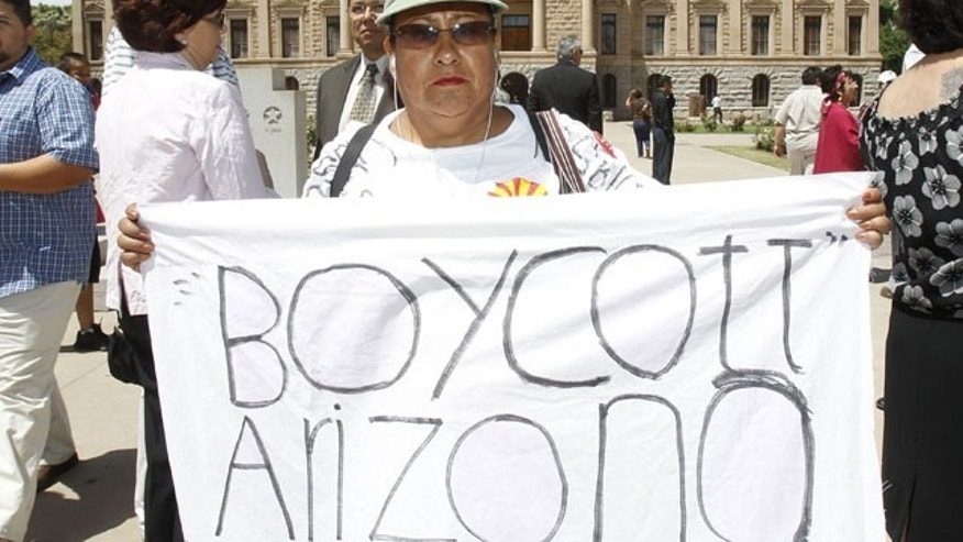 April 29: Josephine Nevarez, of Phoenix, holds a sign in protest as she attends a news conference where it was announced that The National Coalition of Latino Clergy and Christian Leaders, with the support of several other activist groups, had filed a lawsuit seeking an injunction preventing authorities from enforcing the new Arizona immigration law at the Arizona Capitol in Phoenix.