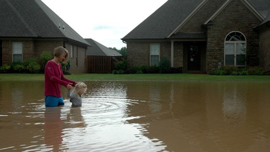 May 1: Kristi Hellerman walks her daughter Kallie Cox, 3, through their flooded neighborhood near Pleasant Planes.