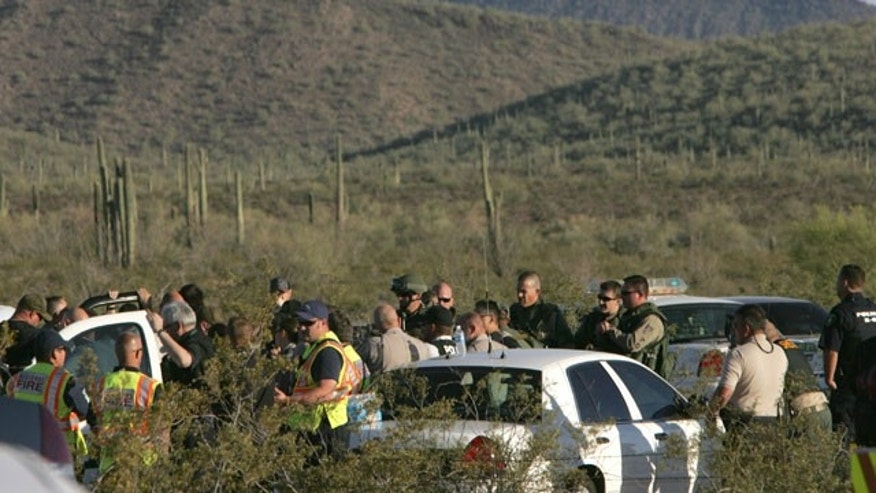 Law enforcement officers from different agencies gather to coordinate the search for a suspect that shot a Pinal County Sheriff's deputy Friday April 30, 2010 in the desert southwest of Stanfield, Ariz. Pinal County sheriff's Lt. Tamatha Villar says the deputy suffered a superficial wound to his abdomen after being shot with an AK-47 assault rifle.