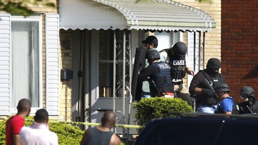 Law enforcement officers enter a duplex on Detroit's east side where police responding to a 911 call at the vacant house were met with heavy gunfire early Monday, May 3, 2010 that killed one officer and wounded four others, authorities said. It was the first time in five years that a Detroit police officer has been killed in the line of duty, Police Chief Warren Evans said.