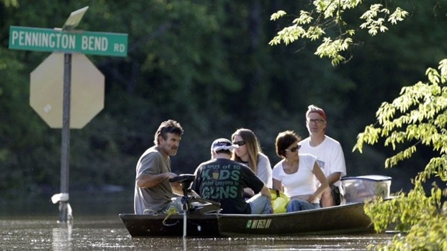 May 5: Scott Burton, left, gives a boat ride to neighbors down a flooded street in Nashville, Tenn.
