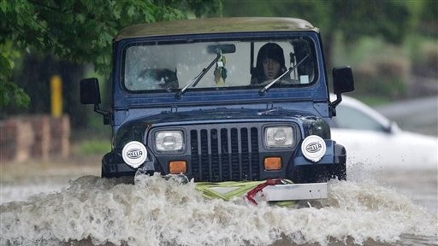 A vehicle is driven through standing water on a flooded street on Saturday, May 1, 2010 in Nashville, Tenn. Widespread flooding is being reported in Tennessee as heavy rains continue to pound the state. Tennessee Emergency Management spokesman Jeremy Heidt said some areas of the state had gotten up to 10 inches of rain by Saturday afternoon and more was expected. (AP Photo/Mark Humphrey)