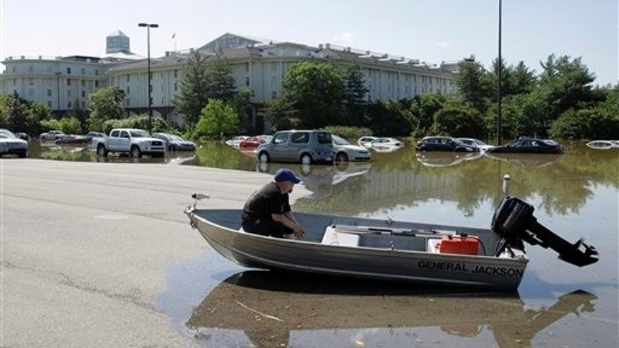 Opryland worker Jason Bowlin sits in a boat in the flooded parking lot of the Opryland Hotel in Nashville, Tenn., on Monday, May 3, 2010. After heavy weekend rains and flooding, officials in Tennessee are preparing for the Cumberland River, which winds through Nashville, to crest more than 11 feet Monday afternoon. (AP Photo/Mark Humphrey)