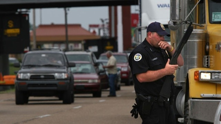May 20: West Memphis, Arkansas police officer J. Langley keeps traffic at a standstill as he blocks an on-ramp next to the already shut down lanes of I-40 at Ingram Blvd. in West Memphis following the killing of two West Memphis police officers.