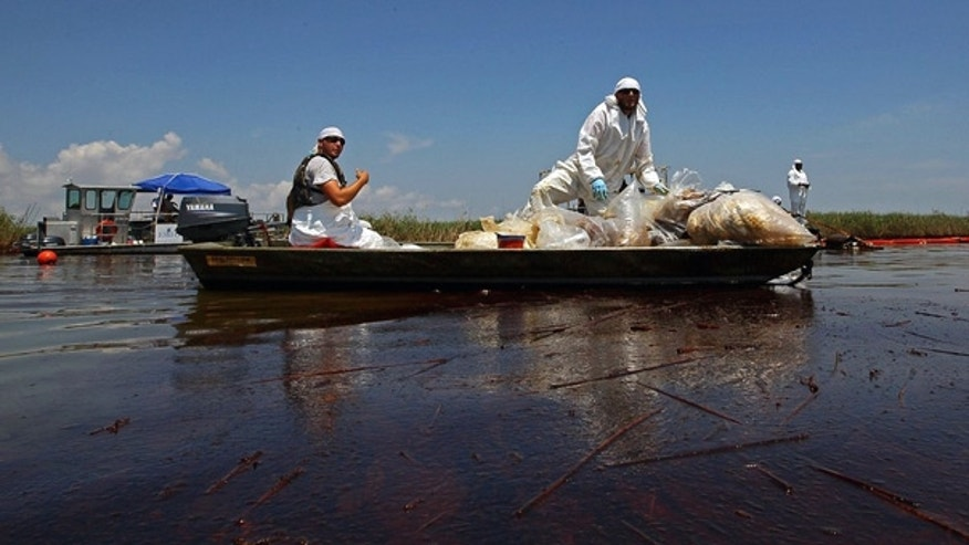June 1: Contract workers from BP ferry oil-soaked waste in a marsh near Pass a Loutre, La.