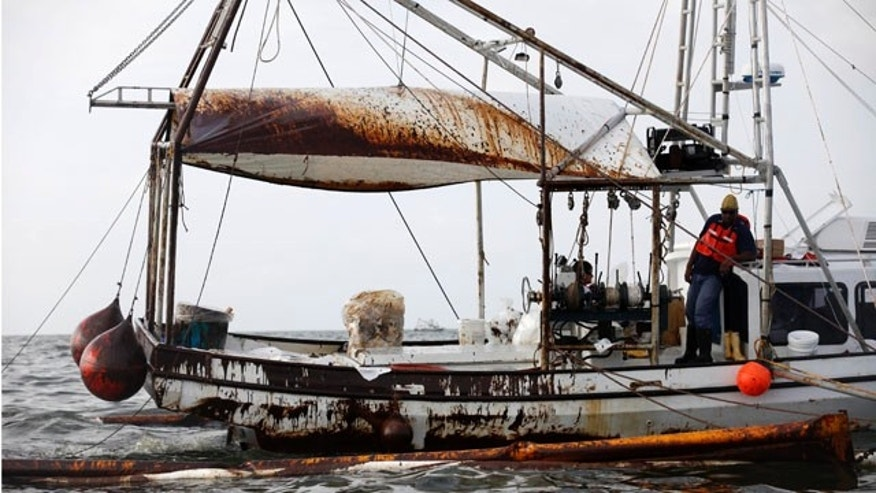 June 4: A fishing trawler covered in oil pulls oil covered booms through Barataria Bay just inland from the Gulf of Mexico in Plaquemines Parish, La