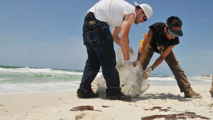 June 4: A crew picks up oil that washed up along Pensacola Beach, Fla. Waves of gooey tar blobs were washing ashore in growing numbers on the white sand of the Florida Panhandle Friday as a slick from the BP spill drifted closer to shore.