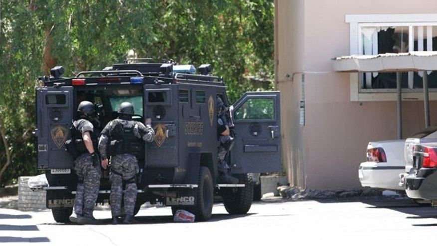 June 10: Law enforcement officers huddle behind an armored vehicle outside an apartment during day two of a hostage standoff as an armed robbery suspect barricaded himself and a 15-month-old boy in Sacramento, Calif.