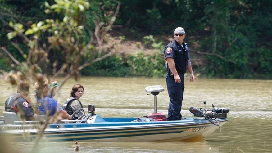 June 12: Officer Les Munn, of Texarkana, Ark., stands at the front of a boat as officials search near the edge of the Little Missouri River near Langley, Ark.