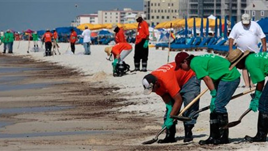 June 12: Oil cleanup workers hired by BP clean oily deposits from the shore in Orange Beach, Ala.