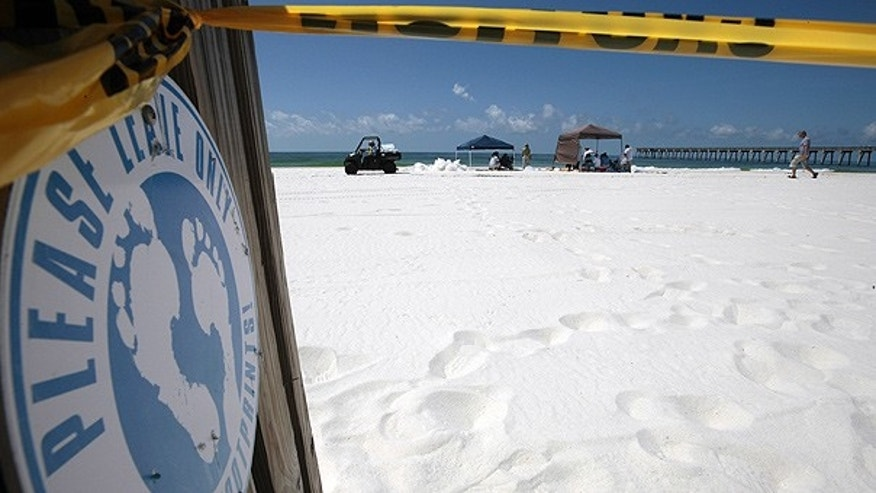 June 24: Police tape guards the public beach in Pensacola Beach, Fla., after officials closed the public beaches to swimmers.