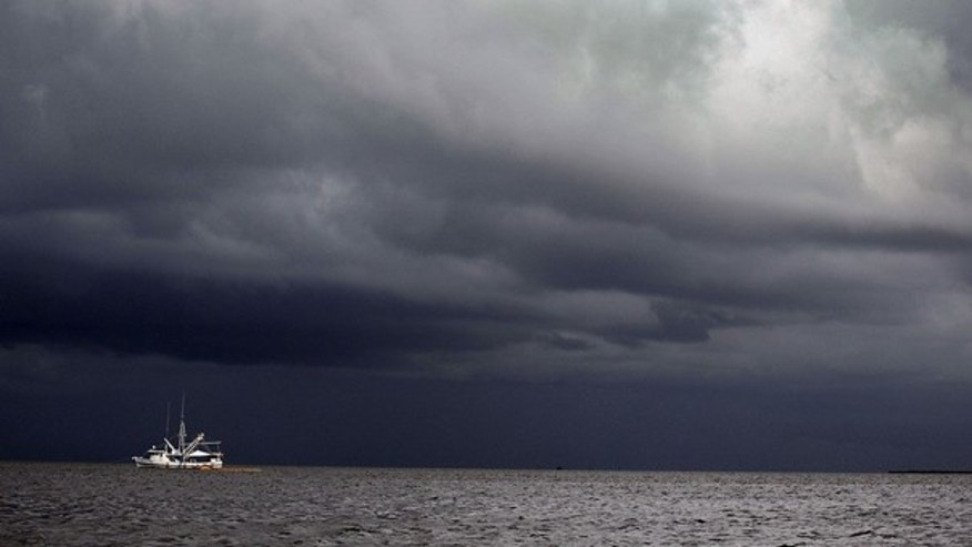 June 28: Storm clouds are seen over a boat using a boom and absorbent material to soak up oil near Grand Isle, La.