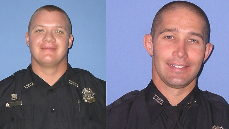 Tampa, Fla., Police Officers David Curtis and Jeffrey Kocab were killed in an early Tuesday shooting during a traffic stop that has prompted a massive manhunt for two people.