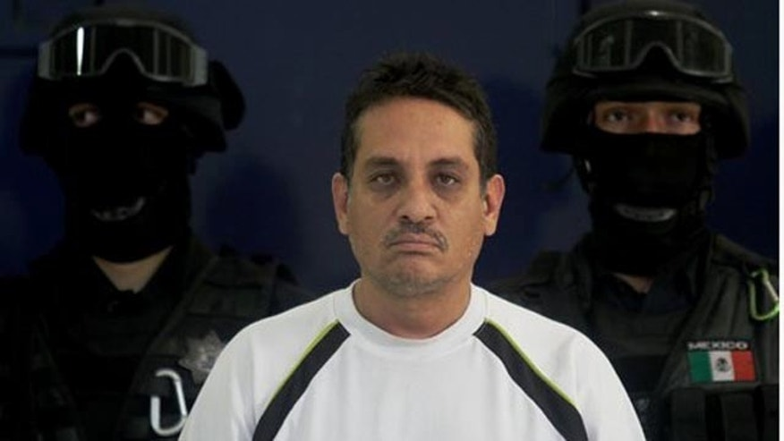 "July 2, 2010: Jesus Ernesto Chavez, known as ""El Camello"" stands as he is guarded by federal police officers during a presentation to the press, in Mexico City. According to the federal police Chavez ordered the March 13 attack that killed a U.S. consulate employee and her husband as they drove in the violent border city."